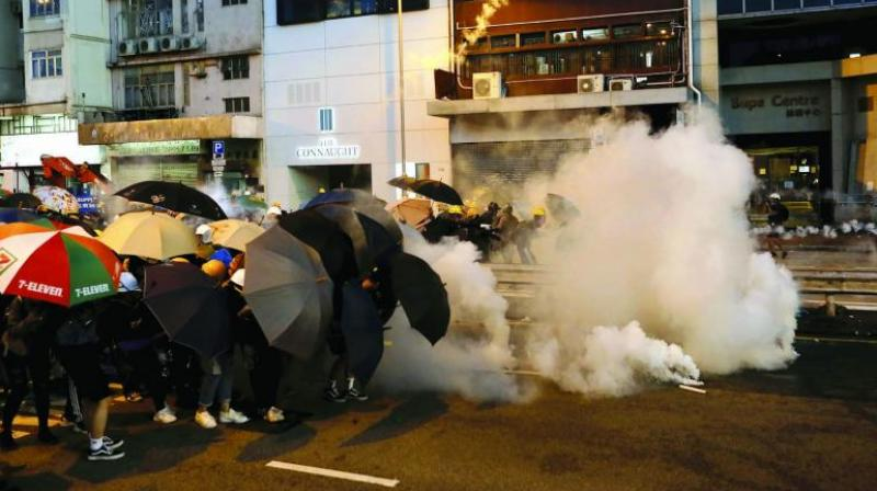 Protesters use umbrellas to shield themselves from teargas fired by policemen as they face off on a street in Hong Kong. (Photo: AP)