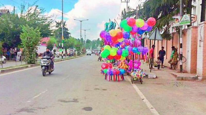 A vendor sells balloons at a street in Srinagar after curfew was relaxed ahead of Id on Sunday, but there appear to be few takers. (Photo: DC)
