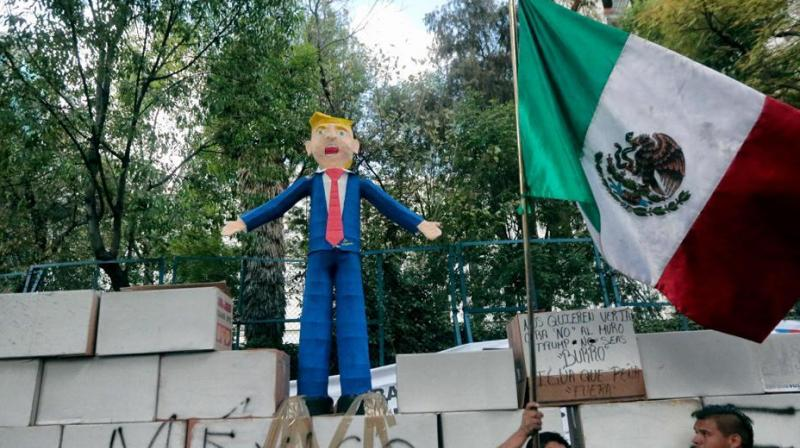 People protest against US President Donald Trump's inauguration next to a fake wall with a Mexican national flag and a dummy representing him in Mexico City.(Photo: AFP)