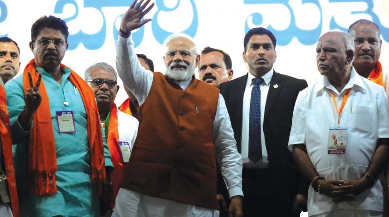 Prime Minister Narendra Modi and BJP leaders B.S. Yeddyurappa and R. Ashok at a campaign programme in Hubballi on Sunday.