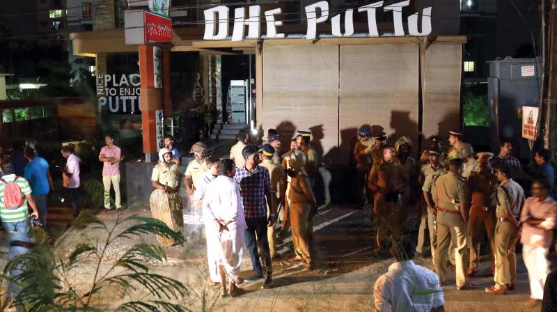 Police personnel and local residents near Dhe Puttu restaurant owned by actor Dileep in Kochi on Monday night. (Photo: ARUNCHANDRA BOSE)