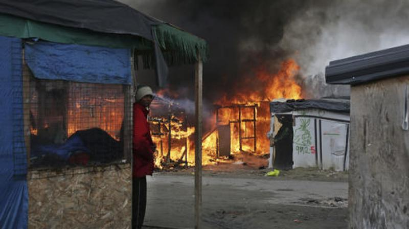 """A man stands next to a burning tent as fires were started in the makeshift migrant camp known as """"the jungle"""" near Calais, northern France .(Photo:AP)"""