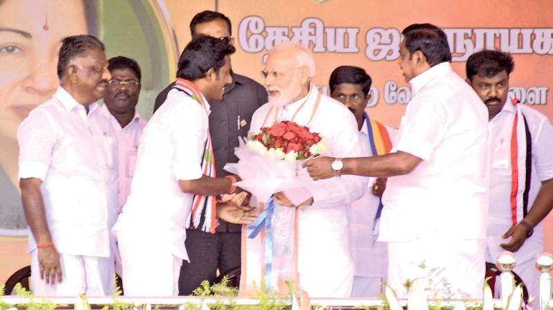 PM Narendra Modi being greeted by AIADMK  candidate Ravindranath at a rally in Theni, as CM Edappadi K. Palaniswami and deputy CM O Panneerselvam  look on. (DC)