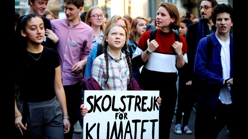"Swedish teenager Greta Thunberg (centre), carrying a sign that reads: ""school strike for the climate"", leads a march of thousands of French students through Paris on Friday. (Photo:AP)"