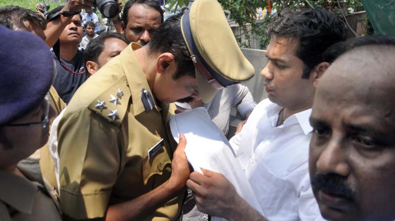 Kochi city police commissioner M.P. Dinesh examines the dhothi of MLA Hibi Eden after he alleged that Consumerfed staff sprinkled urine at people protesting against a retail liquor outlet of Consumerfed at Ponnurunni in Kochi on Thursday. (Photo:  SUNOJ NINAN MATHEW)