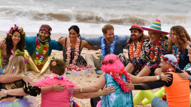 """Britain's Prince Harry and his wife Meghan, Duchess of Sussex join a circle during a """"Fluro Friday"""" session run by OneWave, a local surfing community group who raise awareness for mental health and wellbeing, at Sydney's iconic Bondi Beach on October 19, 2018. (Photo: AFP)"""