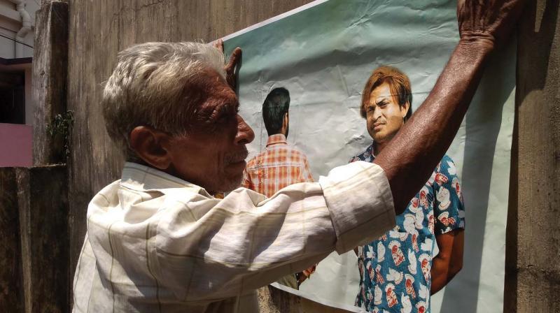 Ramabhadran engaged in pasting cinema posters in Thiruvananthapuram on Tuesday.