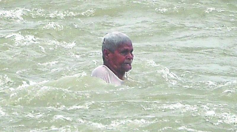 Majji Appanna is swept away by water released through the five gates of the Prakasam barrage that were lifted on Saturday. (Photo: Ch. narayana Rao)
