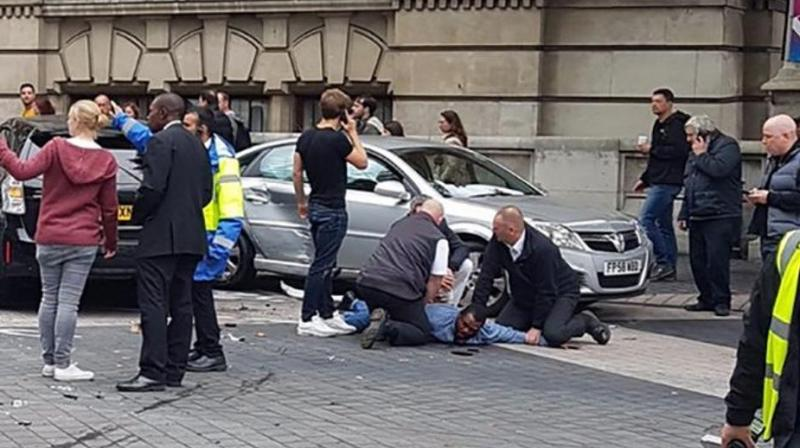A handout picture obtained from the twitter user @StefanoSutter shows a man being restrained alongside vehicles (centre R) on Exhibition Road, in between the Victoria and Albert museum and the Natural History Museum, in London on October 7, 2017. (Photo: AFP)