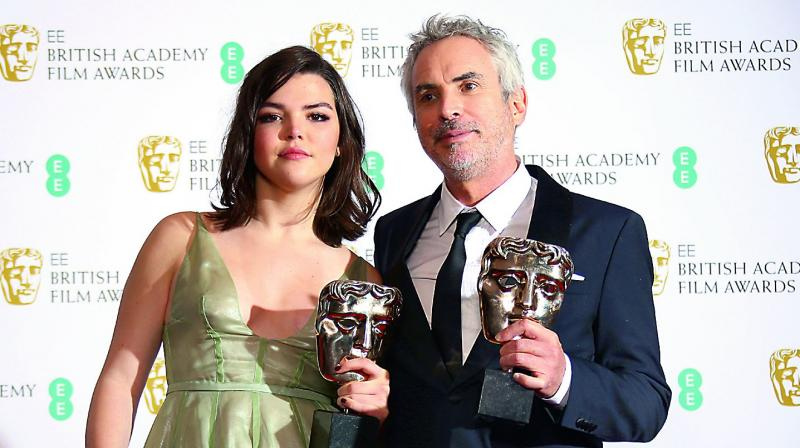 Director Alfonso Cuaron poses with daughter Tess Bu Cuaron for photographers backstage with his Best Film and Best Director Award for his film 'Roma' at the BAFTA awards in London on Sunday. 	–AP