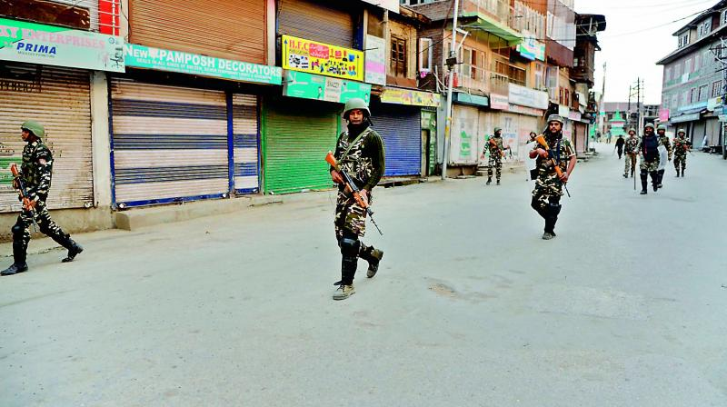 Security personnel patrol along a street in Srinagar as widespread restrictions on movement and a telecommunications blackout remained in place.  (AFP)