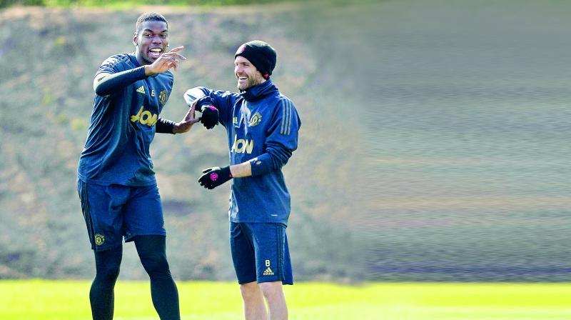 Manchester United's Paul Pogba trains with teammate Juan Mata in Manchester on Tuesday.	(Photo: AP)