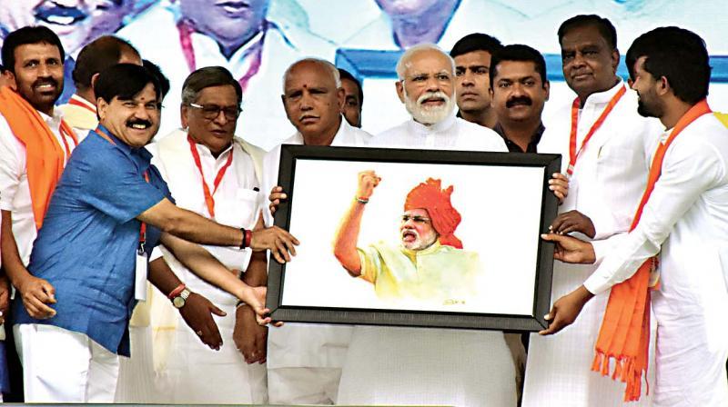 BJP leaders S.M. Krishna, B.S. Yeddyurappa and others present a portrait to PM Modi in Mysuru on Tuesday (Photo: KPN)