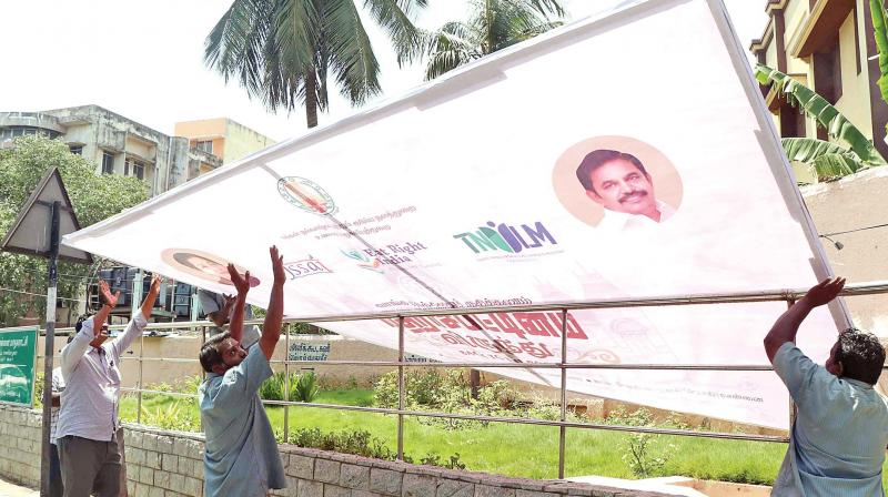 Banners being removed on Santhome high road after Madras high court's order. (Photo: DC)