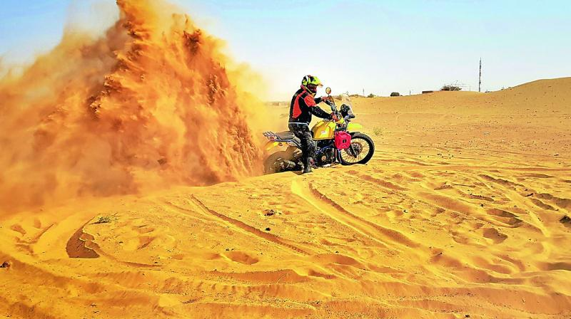 Pruthu doing a bike stunt on the sand dunes