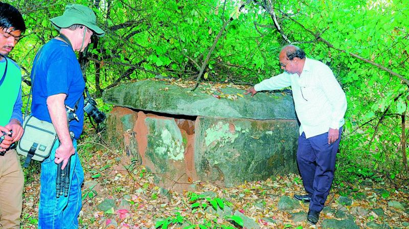 Archaeologists examine a dolmen at Dameravai in Tadwai mandal of Jaishankar Bhupalapally district.