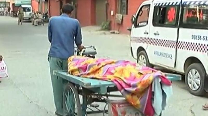 A labourer was compelled to carry his father's body on a cart as he was unable to pay Rs 400 to a private ambulance carrier. (Photo: Videograb/ANI)