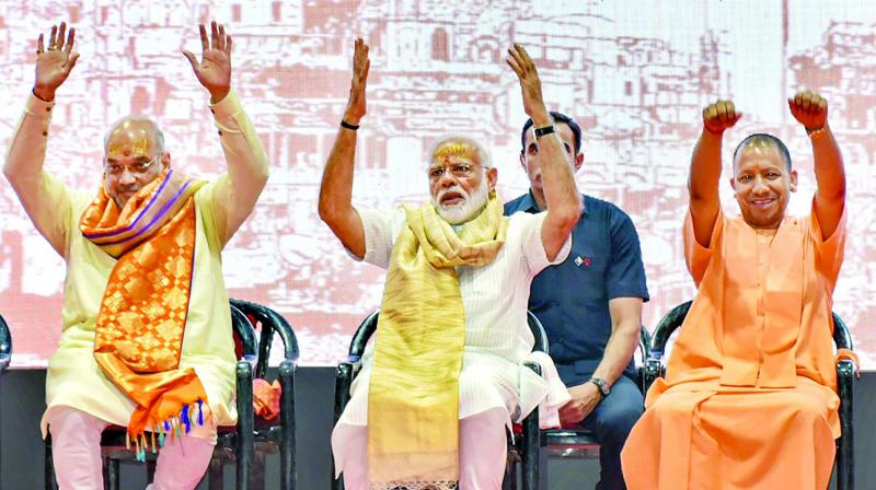 Prime Minister Narendra Modi with BJP president Amit Shah and UP CM Yogi Adityanath during a meeting with the party workers in Varanasi on Monday. (Photo: AP)