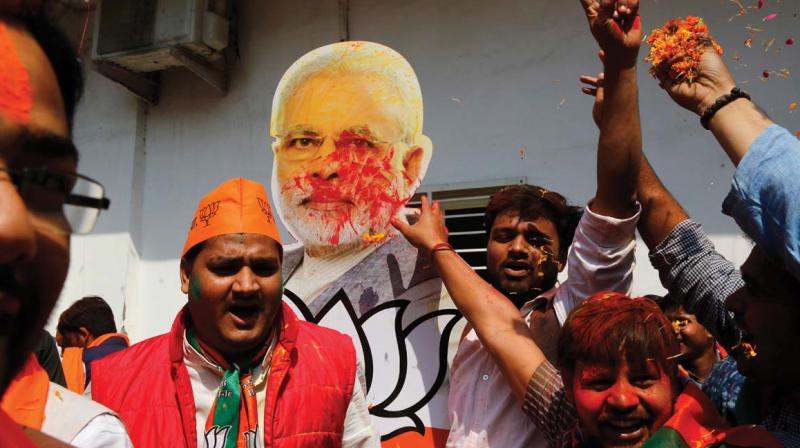 Bharatiya Janata Party supporters raise a cutout of Indian Prime Minister Narendra Modi as they celebrate winning seats in the state of Uttar Pradesh in Lucknow. —AP FILE PIC