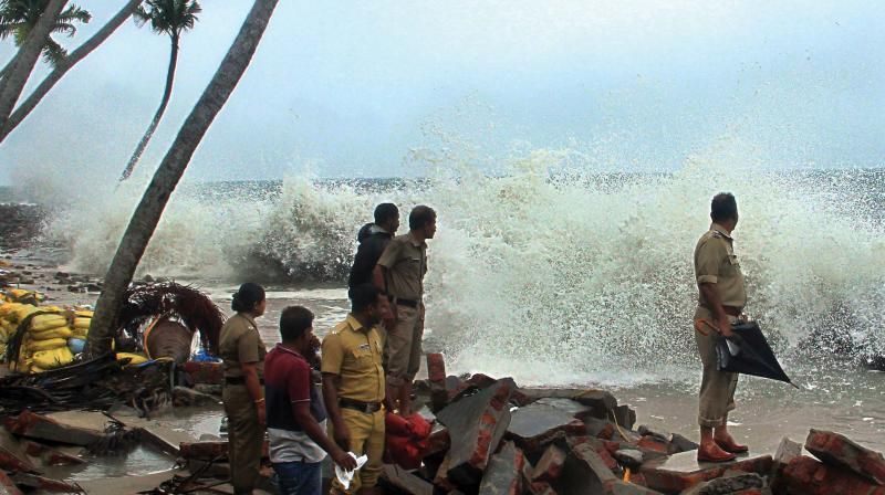 As pre-monsoon rains intensified, sea turned rough in many coastal areas. Residents and police officials of Chellanam watch the rough sea. (Photo: Arunchandra Bose)