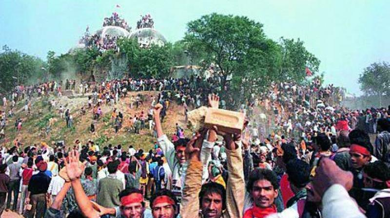 In this file photo, kar sevaks celebrate after demolishing the Babri Masjid in Ayodhya on December 6, 1992.