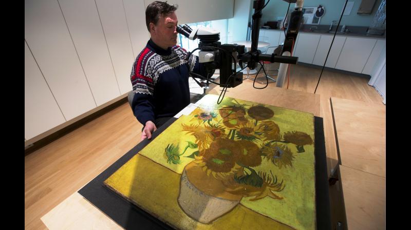 Senior paintings conservator Rene Boitelle works on restoring Vincent van Gogh's world-famous