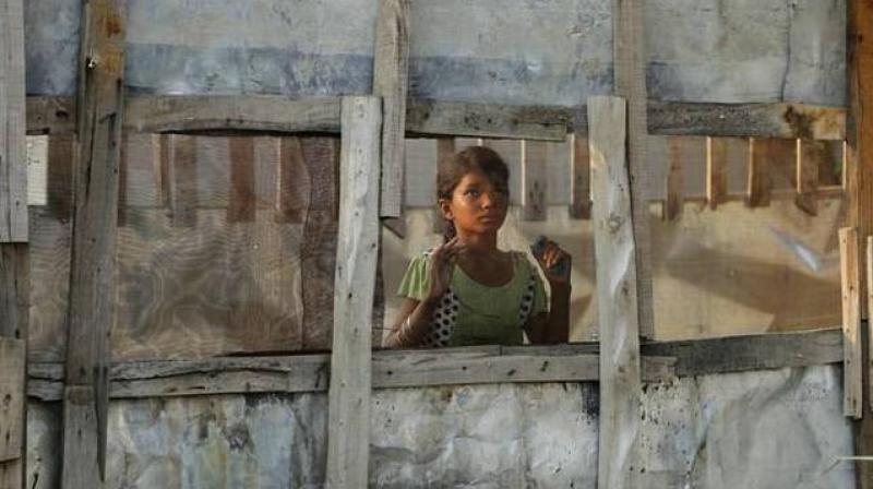 In this August 16, 2017 photo, a Rohingya refugee girl looks through a mesh window at a camp set up for the refugees on the outskirts of Jammu. (Photo: AP)