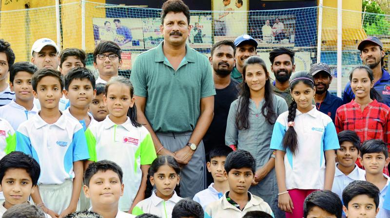 Indian football player G. Soumya (third from right) poses with Sarojini Cricket and Tennis Academy secretary G. Kiran Reddy (centre) and SCTA trainees during the felicitation function in Hyderabad.