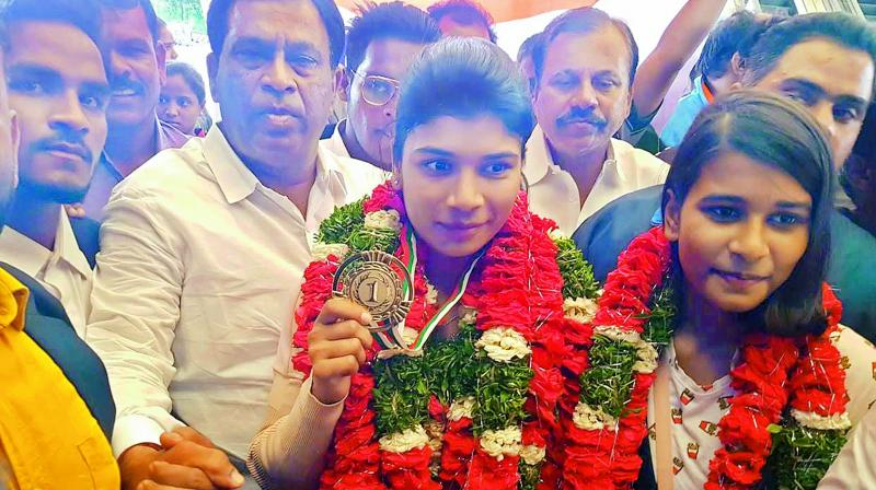 Boxer Nikhat Zareen (centre) shows off her gold medal after arriving in Hyderabad on Monday. She is flanked by sister Afnan (right), a state level badminton player, and Sports Authority of Telangana State chairman Allipuram Venkateshwar Reddy (left).