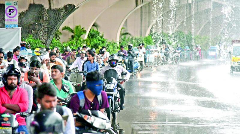 Bikers are forced to take shelter from the heavy rains under a flyover (Photo: S. Surender Reddy)