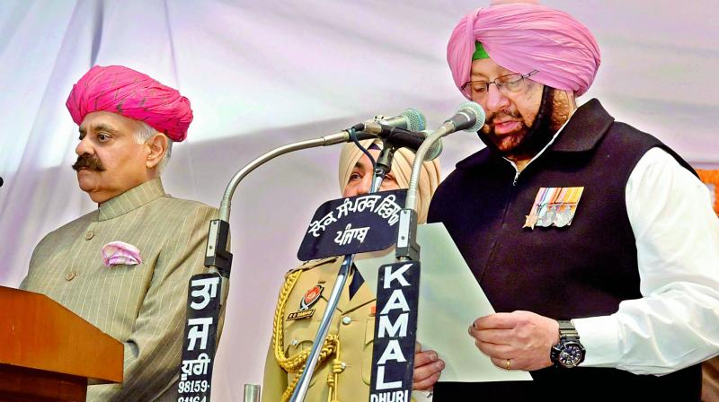 Punjab Governor V.P. Singh Badnore administering oath to the new Punjab Chief Minister Amarinder Singh at the Raj Bhavan in Chandigarh on Thursday. Also sworn into the Cabinet was former cricketer Navjot Singh Sidhu (not in picture), who, as per TV reports, was seen touching Amarinder's feet after the event. (Photo: PTI)
