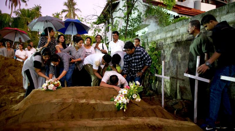 Relatives place flowers after the burial of three victims of the same family, who died at Easter Sunday bomb blast at St Sebastian Church in Negombo. (Photo: AP)