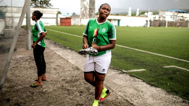Two members of the FC Mamans national football team, Armelle Sylva and Hairiat Abdourahmane, get ready for their training session. (Photo: AFP)