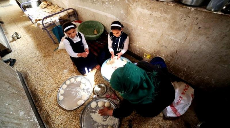 Um Yusuf, a widow of an Islamic State group militant and her daughters make bread to sell in Mosul, Iraq. (Photo: AP)