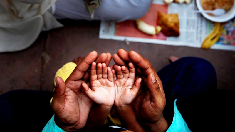 An Indian Muslim father holds the hands of his daughter in his palms and prays before breaking fast on the first day of holy month Ramadan at the Jama Mosque in New Delhi, India. (Photo: AP)
