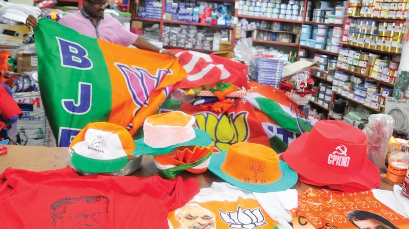 A shopkeeper keeps accessories of various political parties ready with Lok Sabha elections around the corner (Photo: DC)