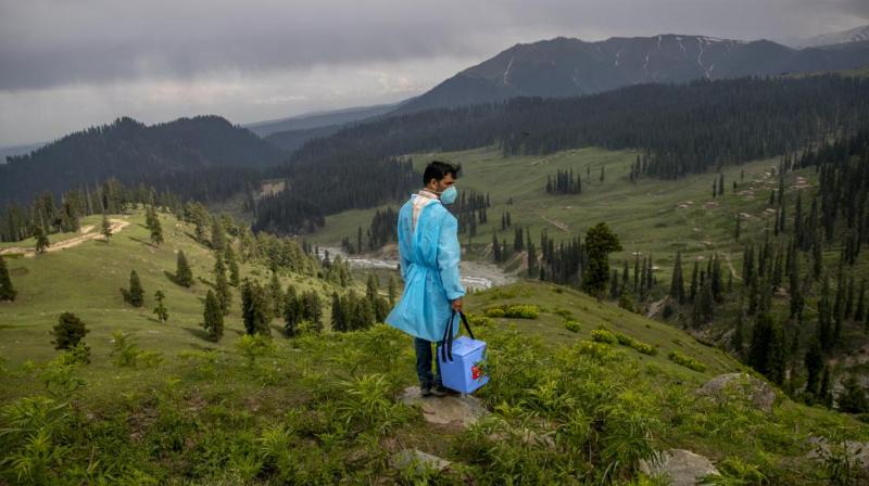 A healthcare worker Nazir Ahmed carries vaccines and looks out from a hillock for Kashmiri shepherds to vaccinate them in Tosamaidan, southwest of Srinagar. The challenge for health workers travelling to to long distances for vaccinating mostly shepherds and nomadic herders in the remote meadows of the Himalayan region has not been the treacherous terrain but to persuade women to get COVID-19 vaccines. (AP Photo)