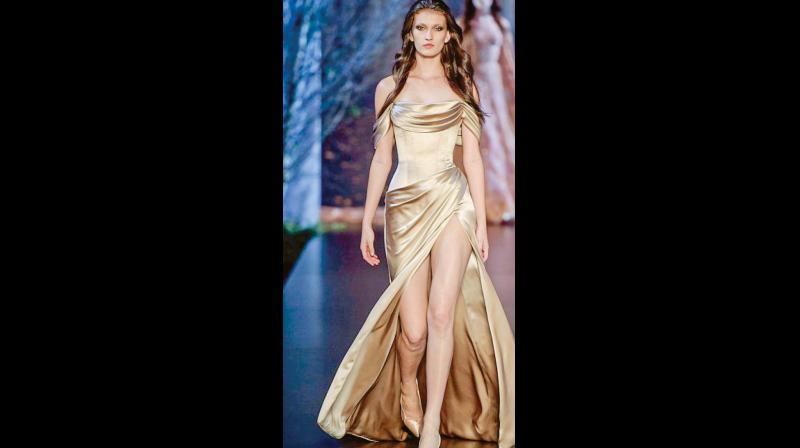 This model is seen wearing a ruched gold dress that is bound to make an instant statement!