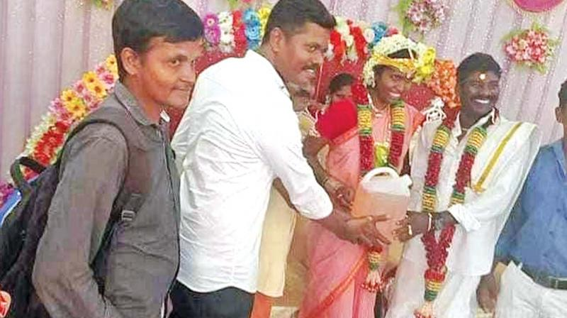 Prabhu(left), gives Elanchezhian and his astonished  just-wedded wife Kanimozhi 5 litres of pertrol, in a can, as a gift on their wedding day. (Photo:DC)