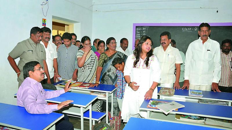 Urban development minister P. Narayana inspects the new furniture in a municipal school at Nellore on Tuesday. Nellore Corporation chief S. Dilli Rao is seen explaining about the infrastructure to the minister. (Photo: DC)