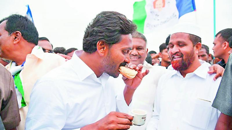 Y.S. Jagan Mohan Reddy relishing a bun and a cup of tea during his padayatra in Tadipatri on Tuesday. (Photo: DC)