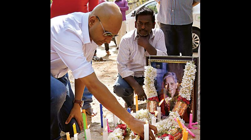 Gauri Lankesh's brother Indrajit lights a candle in Chamarajpet on Monday. (Photo: DC)