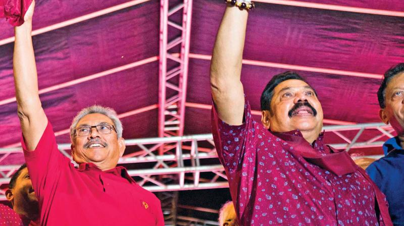 SLPP party presidential candidate Gotabhaya Rajapaksa and his brother Mahinda Rajapaksa wave at supporters during a campaign rally in Homagama on Tuesday. (Photo: DC)