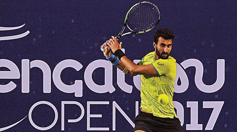 Yuki Bhambri plays a return to N. Sriram Balaji in the opening round of the ATP Bengaluru Open, at the KSLTA Stadium in Bengaluru on Tuesday. (Photo: SHASHIDHAR B.)