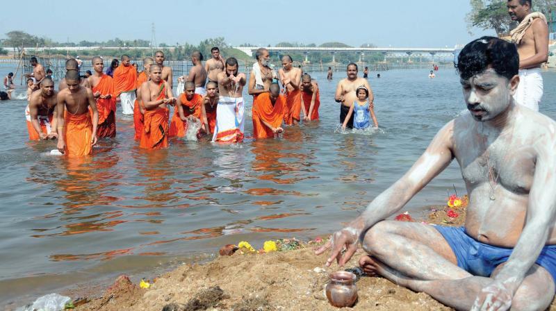 Devotees perform rituals at Kumbh Mela at T Narasipura near Mysuru on Sunday.
