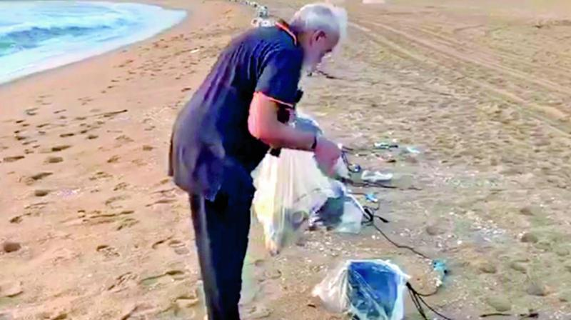 Prime Minister Narendra Modi takes a stroll on the beach while picking up litter. (Photo: DC)