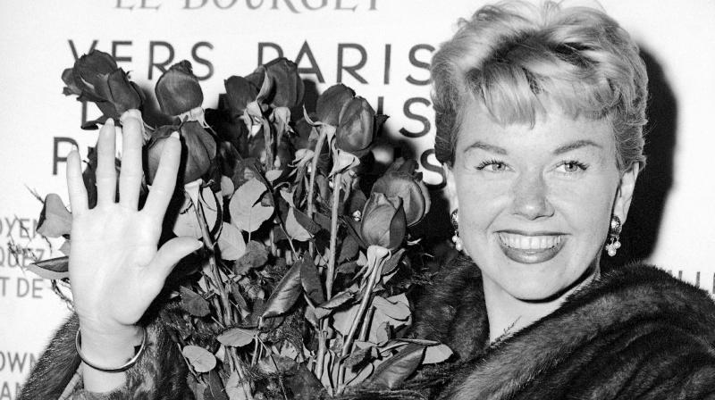 In this April 15, 1955, file photo, American actress and singer Doris Day holds a bouquet of roses at Le Bourget Airport in Paris after flying in from London. The Doris Day Animal Foundation confirmed Day died early Monday, May 13, 2019, at her home in Carmel Valley, Calif. She was 97. (Photo: AP)