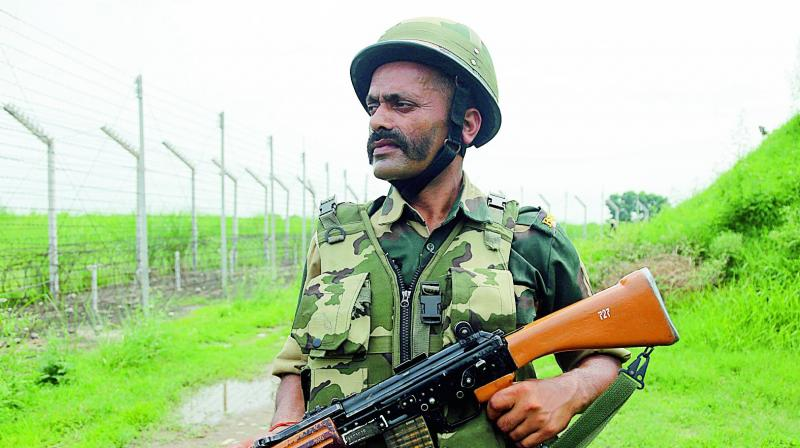 A BSF soldier patrols near the India Pakistan border fencing at Garkhal in Akhnoor, about 35 kms west of Jammu on Tuesday. (Photo: AP)