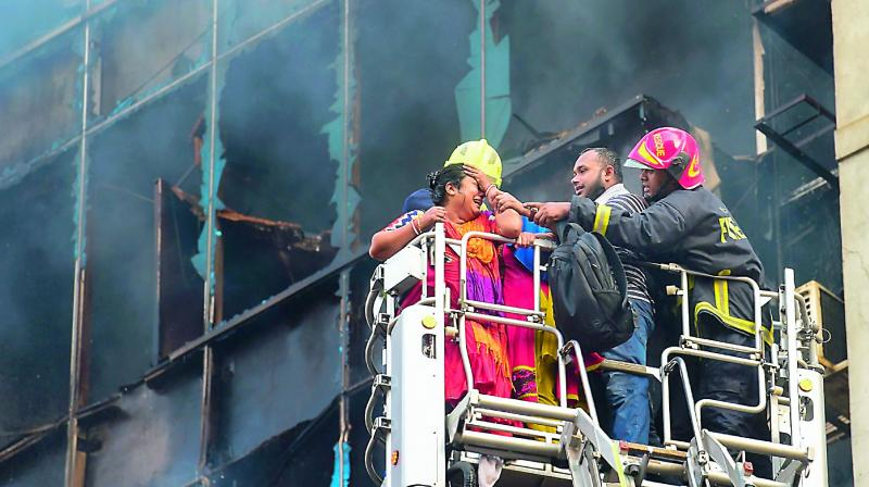A Bangladeshi survivor reacts after being rescued by firefighters from a burning office building in Dhaka on Thursday. A huge fire tore through a Dhaka office block killing at least seven people with many others feared trapped in the latest major inferno to hit the Bangladesh capital. –AFP