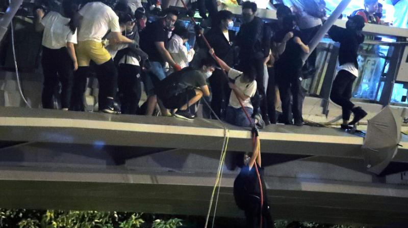 Dozens of Hong Kong pro-democracy protesters dramatically escaped a two-day police siege at a university campus late Monday by shimmying down ropes from a bridge to waiting motorbikes, after Beijing again warned it could intervene to end the crisis engulfing the city. (Photo: AFP)